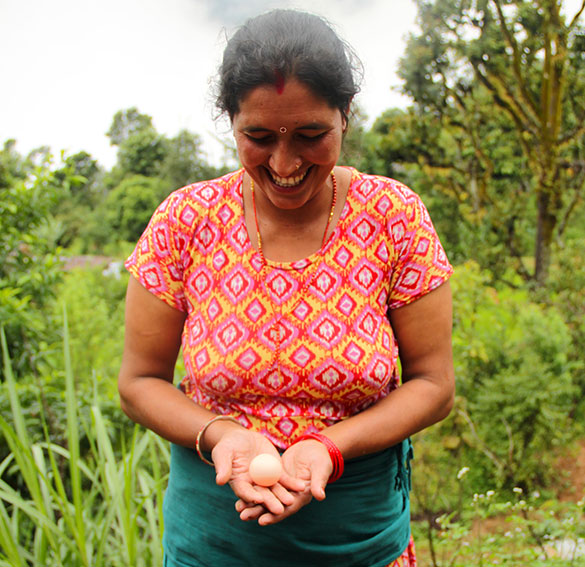 Photo of a woman smiling and holding an egg in a garden.