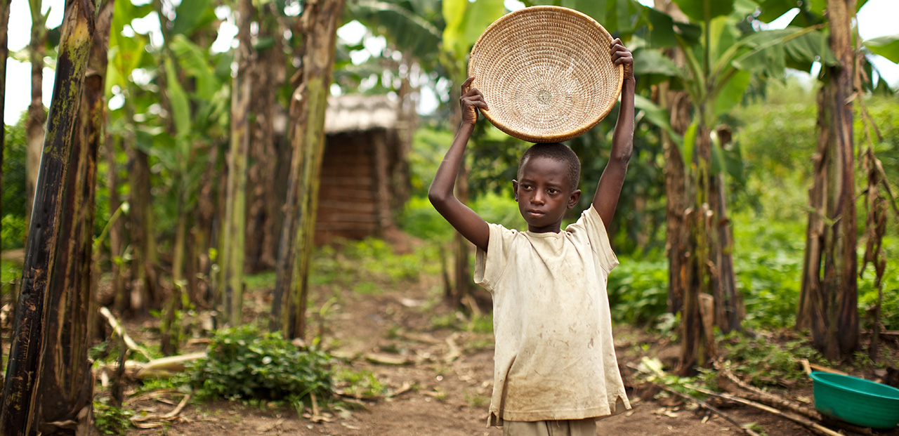 Photo of a boy holding a large bowl in a forest