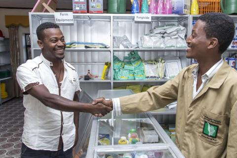 Two men shaking hands at a store